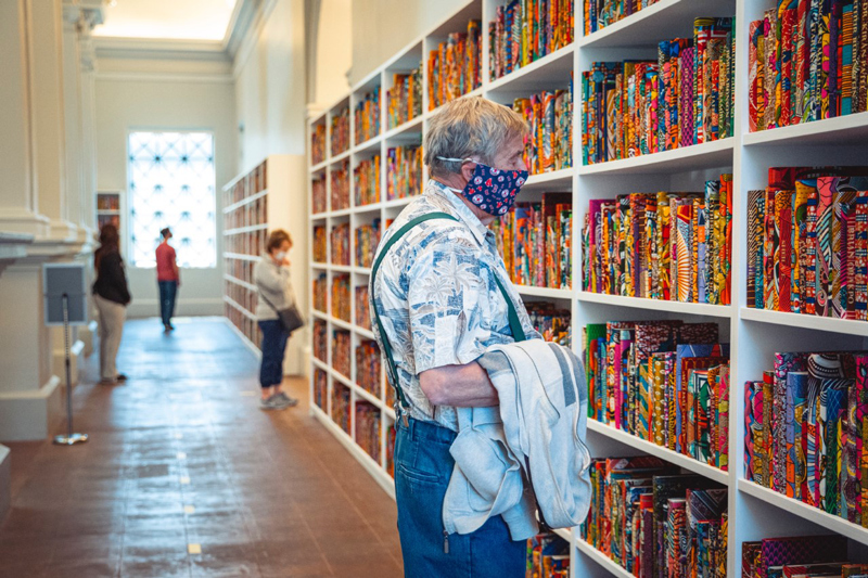 "A museum visitor looking at Shonibare's ""The American Library"""